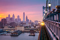 Philadelphia under a hazy purple sunset an incoming train crosses ben franklin bridge Stock Photography