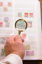 Philatelist looking at stamps magnifying glass held in a hand by to view an old stamp in an album Stock Images