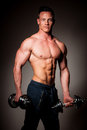 Phisique fitness competitor poses in studio after workout in gym showing muscles Royalty Free Stock Image