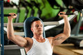 Phisique fitness competitor works out in gym lifting dumbbells physique to have healthy and muscular body Stock Photo