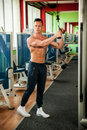 Phisique fitness competitor works out in gym lifting dumbbells physique to have healthy and muscular body Royalty Free Stock Image