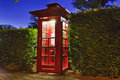 Phone box red sydney historic wooden at sunset with illumination in the street of point of voice communication for public access Royalty Free Stock Images