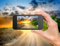 Phone and evening landscape mobile in hand Royalty Free Stock Photography