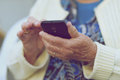 Phone in the hands of an elderly woman Royalty Free Stock Photo
