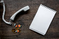 Phone handset, multicoloured pills and notebook on dark wooden desk top view call doctor mock up Royalty Free Stock Photo