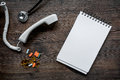 Phone handset, pills, phonendoscope and notebook on dark wooden desk top view call doctor mock up Royalty Free Stock Photo