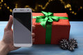 Phone in his hand on the background of christmas tree Royalty Free Stock Photo