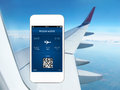 Phone with mobile wallet and plane ticket white against the background of the window blue sky airplane wing Stock Images