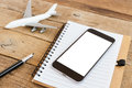 Phone screen and airplane model on wood table Royalty Free Stock Photo
