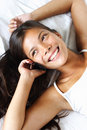 Phone woman talking on bed - asian model Royalty Free Stock Photo