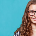 A photo of beautiful girl portrait young curly haired student wearing trendy glasses and posing over turquoise background hipster Stock Photos