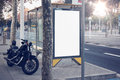 Photo blank lightbox on bus stop in the modern city. Authentic motobike parking close. Horizontal mockup, sunlight Royalty Free Stock Photo