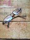 Broken eyeglass at wooden board