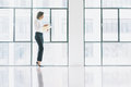 Photo business woman wearing modern suit, looking  mobile phone and holding papers in hands. Open space loft office Royalty Free Stock Photo