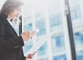Photo business woman wearing suit, looking smartphone and holding documents in hands. Open space loft office. Panoramic windows ba Royalty Free Stock Photo