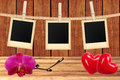 Photo cards hanging on rope on clothespins, orchid and red hearts Royalty Free Stock Photo