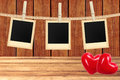 Photo cards hanging on rope on clothespins and two red hearts Royalty Free Stock Photo