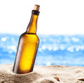 Photo of cold beer botle in the sand. Royalty Free Stock Photo