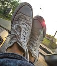 Photo depicting tennis shoes resting on a car dashboard. Royalty Free Stock Photo