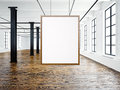 Photo of empty interior in modern loft. Open space loft.Empty white canvas hanging on the wood frame. Wood floor, bricks Royalty Free Stock Photo