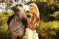 Photo fashionable beautiful blonde woman posing horse green garden Royalty Free Stock Images
