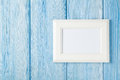 Photo frame on blue wooden wall Royalty Free Stock Photo