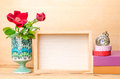 Photo frame with books and flowers on the wooden table Royalty Free Stock Photo