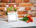 Photo frame with bouquet of tulips on a white table Stock Photo