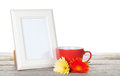 Photo frame with red cup and twocolorful gerbera flowers Royalty Free Stock Photo