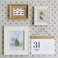 Photo frames and calendar hanged on wall Royalty Free Stock Photo