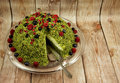 Photo of green spinach cake with forest fruits on a wooden count Royalty Free Stock Photo