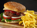 Photo of a hamburger and french fries on a wooden board Royalty Free Stock Photos