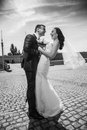 Photo of handsome groom hugging bride on paving road Stock Photography
