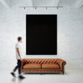 Photo of man in gallery. Waching black empty canvas hanging on the brick wall and vintage classic sofa wood floor Royalty Free Stock Photo