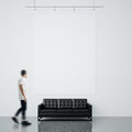 Photo of man in gallery. Waching empty canvas hanging on the brick wall and black generic design sofa concrete floor Royalty Free Stock Photo