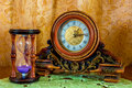 Photo of an old clock and sandglass on brown background