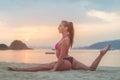 Photo in profile of slim fitness model with brown hair wearing bikini doing leg split exercise on beach at sunrise