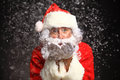 Photo of Santa Claus in eyeglasses blowing snow Royalty Free Stock Photo