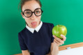 Photo of sassy student shows tongue and holding an apple near blackboard Royalty Free Stock Photo