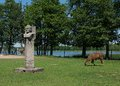 Photo of soviet sculpture and domestic animals walking near in grutas park lithuania grutas is a sculpture park of soviet era and Stock Photos