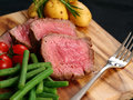 Photo of steak dinner with thick slices of sirloin cherry tomatoes green beans and potatoes on a wooden board Stock Image