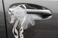 A photo taken on a wedding car door handle with ribbons bow and flower arrangements Royalty Free Stock Images