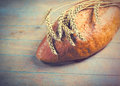 Photo of tasty fresh loaf of bread and branch of wheat on the wo Royalty Free Stock Photo