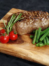Photo of a thick sirloin steak dinner with rosemary cherry tomatoes and green beans on a wooden board Royalty Free Stock Photo