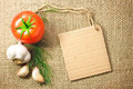 Photo of tomato and garlic vegetables and price tag on sacking background texture Royalty Free Stock Photo