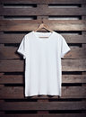 Photo of white tshirt hanging on wood background. Vertical blank mockup
