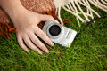 Photo of woman holding compact camera on grass closeup Royalty Free Stock Photo