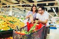Young cheerful loving couple in supermarket with shopping trolley choosing fruits Royalty Free Stock Photo