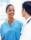 Photo of a young nurse looking at doctor, smiling Royalty Free Stock Images