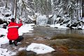 Photograph in red jacket with digital camera in hands is taking photo of winter waterfall frozen Royalty Free Stock Photos